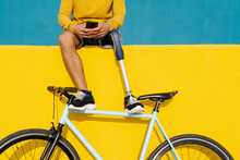 Young Disabled Man With Bicycle Using Mobile Phone While Sitting On Multi Colored Wall