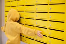 Kid Peeking In Yellow Mailboxes