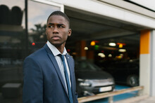 Serious Black Manager Looking Away In Airport Parking Lot