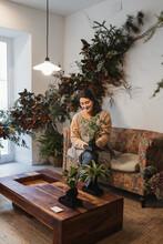 Happy Adult Woman Among Lush Foliage Of Houseplants At Home