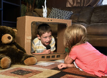 Children Playing Inside Cardboard Television Box