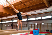 Young Artistic Gymnast Woman Performing And Training On Balance Bar