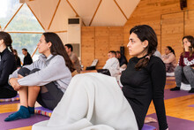 People Sitting On Floor And Listening To Trainer In Light Room