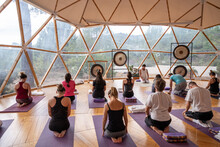 People Doing Yoga On Yoga Mats In Domed Hall