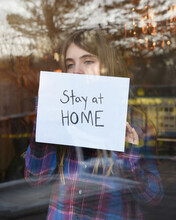 Girl Holding A Stay At Home Sign In Window