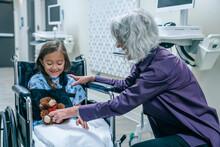 Doctor Giving Teddy Bear To Girl In Wheelchair