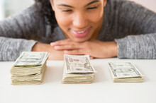 Mixed Race Woman Counting Stacks Of Money