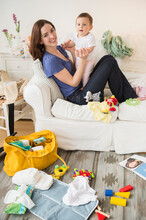 Mother And Baby Playing In Messy Living Room
