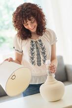 Hispanic Woman Changing Light Bulb