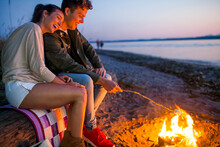 Caucasian Couple Roasting Marshmallows On Fire At Beach
