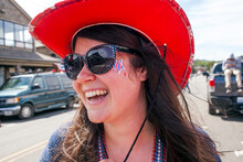 Caucasian Woman Wearing Cowboy Hat And Face Paint In Street