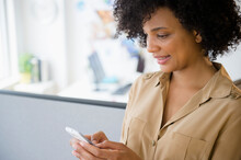 Businesswoman Using Cell Phone In Cubicle