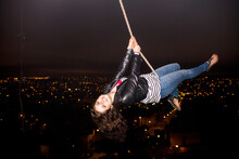 Caucasian Woman On Rope Swinging Over Scenic View Of Cityscape