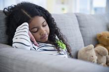 Sad Mixed Race Girl Sitting On Sofa