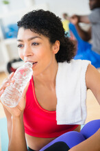 Close Up Of Woman Drinking Water Bottle In Gym