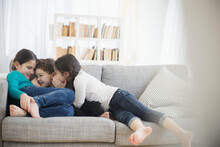 Caucasian Brother And Sisters Whispering On Sofa
