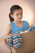 Girl Holding Box Of Clothing For Donation
