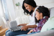 Mother And Daughter Using Laptop On Sofa