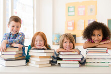 Students Resting On Stacks Of Books In Classroom
