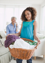 Girl Holding Laundry Basket With Grandmother On Phone In Background