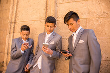 Hispanic Boys Wearing Suits Texting On Cell Phones