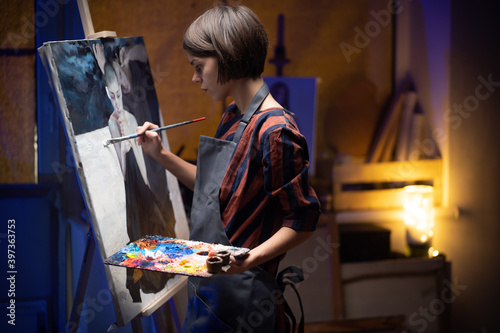 .Female artist Working on oil painting. In her hands are brushes and a palette. Wallpaper Mural