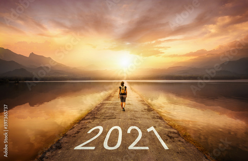 New year 2021 written in the middle of asphalt road with walking girl at sunset.