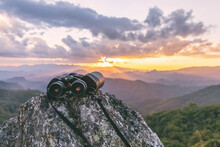 Binoculars On Top Of Rock Mountain At Sunset