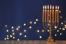 Golden Menorah With Burning Candles On Table Against Blue Background And Blurred Festive Lights, Space For Text