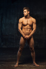 Full Length Portrait Of Naked Man Standing Sideways. Muscled Male Body At Dark Background. Handsome Nude Hunk Covering Himself With Hands.