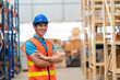 Leinwandbild Motiv Confident smiling Asian male warehouse worker in safety vest and helmet standing with arms crossed in storage warehouse with shelf pallet spare parts parcel background