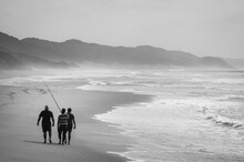 Three Fisherman Walking On The Indian Ocean Beach With Their Rods In A Foggy Day. KwaZulu-Natal, South Africa