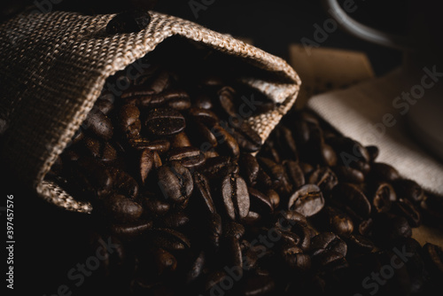 Fototapeta Coffee beans scattered from a linen bag on a wooden table with a vietnamese metal coffe filter. Fresh coffee beans. obraz