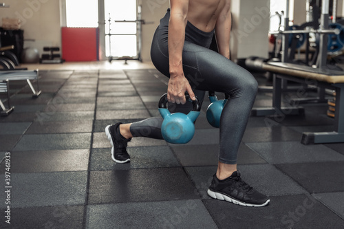 Photo Young muscular woman in sportswear trains lunges with a kettlebells in the gym