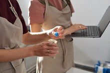 Hand Of Female In Apron Putting Handmade Blue Glass Bead Into Small Linen Sack