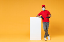 Full Length Delivery Employee African Man In Red Cap T-shirt Face Mask Gloves Work Courier Dealer Service Hold Big White Empty Blank Billboard For Promo Copy Space Isolated On Yellow Background Studio