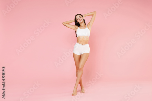 Obraz Full length of beautiful tender young brunette woman in white underwear showing fit sexy body posing hold hands behind head keeping eyes closed isolated on pastel pink background, studio portrait. - fototapety do salonu