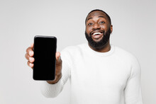 Cheerful Funny Young African American Man 20s Wearing Casual Basic Sweater Hold Mobile Cell Phone With Blank Empty Screen Mock Up Copy Space Isolated On White Color Wall Background Studio Portrait.