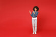 Full length excited little african american kid girl 12-13 years old in denim jacket pointing index fingers aside up isolated on red background children studio portrait. Childhood lifestyle concept.
