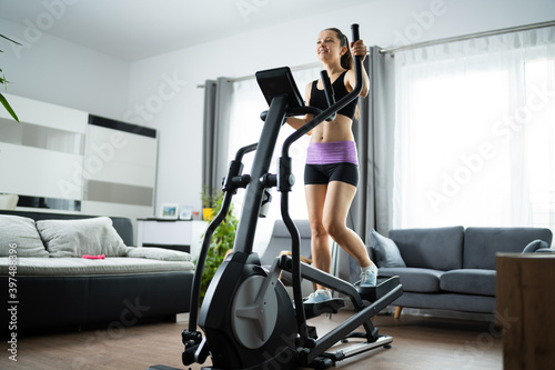 Slika na platnu Woman Training On Elliptical Trainer