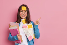 Positive Female Office Worker With Folders And Stickers Wears Round Glasses And Blue Jumper Points Away On Copy Space Gives Recommendation How To Prepare Successful Project Makes Presentation