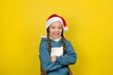 Teen Beautiful Girl With Two Long Braids In Santa Hat Smiling Isolated On Yellow Background.