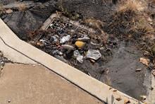 Mud And Trash In A Storm Drain Beside A Clean Sidewalk, Pollution, Horizontal Aspect