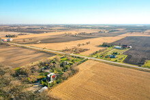 Beautiful Aerial Of Farm Land Including Barns, Silos And A Patchwork Of Agricultural Fields In Rural Wisconsin In Autumn With Patches Of Trees Scattered Throughout The Landscape.