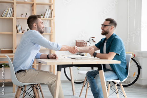 Smiling businessmen shake hands close deal after successful interview in office. Happy employer handshake candidate or business partner make agreement or get acquainted at meeting. Employment concept.