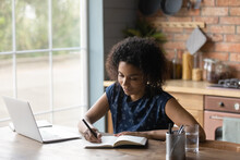 Smiling Young Multiracial African Businesswoman Writing Notes In Paper Notebook, Planning Workday Activities. Happy Millennial Biracial Lady Handwriting In Diary, Sitting At Table Alone At Home.