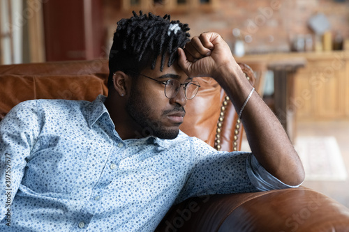 Photo Frustrated young african ethnicity man in glasses sitting on sofa, thinking or life problems, feeling stressed or disappointed alone at home