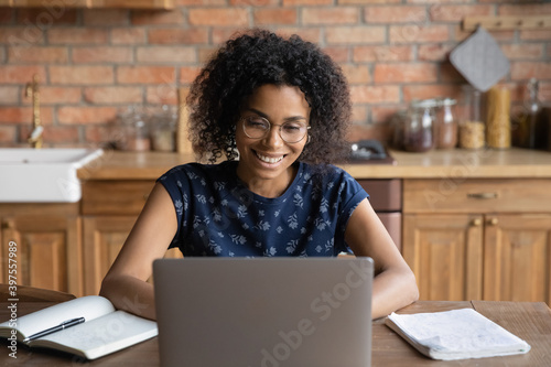 Fototapeta Happy young african american woman in eyeglasses working on computer in kitchen, smiling millennial mixed race female freelancer enjoying using laptop application, web surfing online at home office. obraz