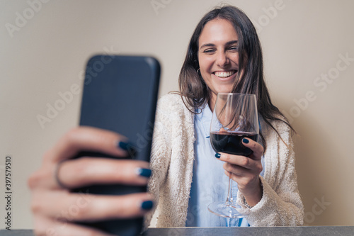 Canvas-taulu young woman smiling and clinking online with red wine having a video call with h