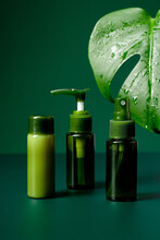 Composition With Bottles Of Organic Essential Oils And Lotions On Green Background. Natural Cosmetics. Beauty Products Package Design.